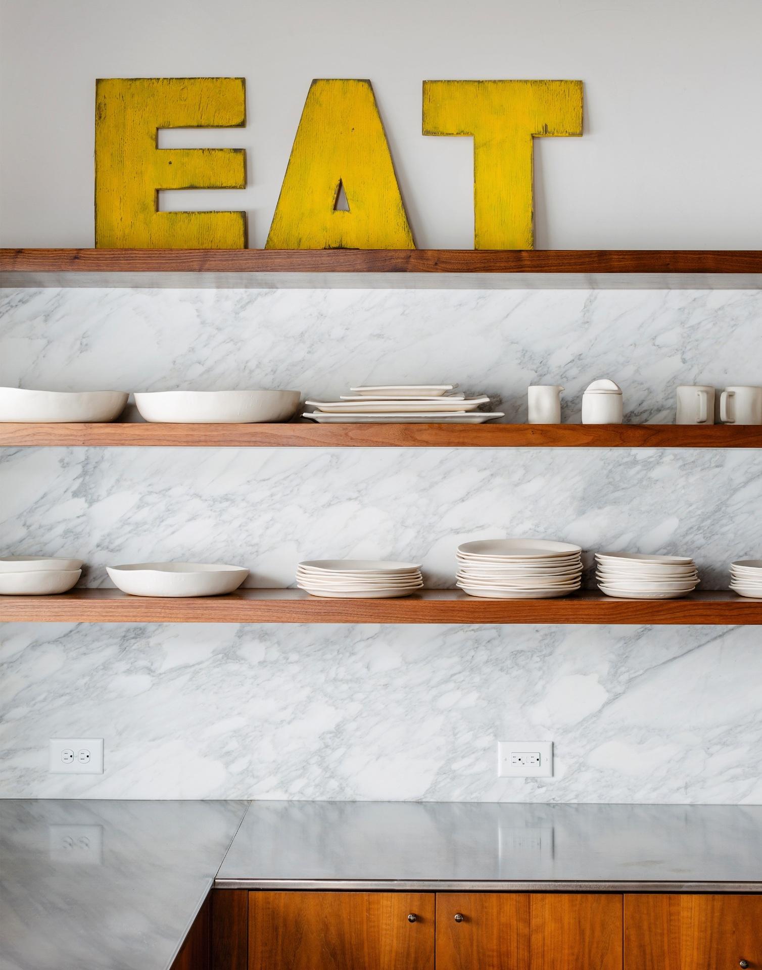Parte dos utensílios ficam acomodados em prateleiras e, assim, ajudam a compor a decoração. As letras amarelas que formam a palavra