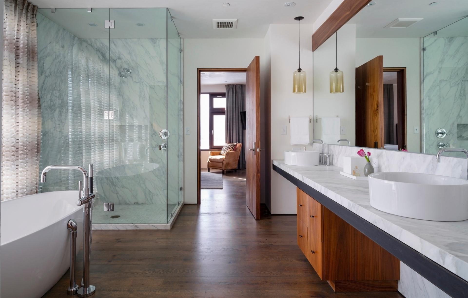 Madeira e mármore criam contraste no banheiro da suíte máster. Sobre a ampla bancada, um delicado pendente Bella Modern, da Niche, auxilia na iluminação (Imagem do NYT, usar apenas no respectivo material)
