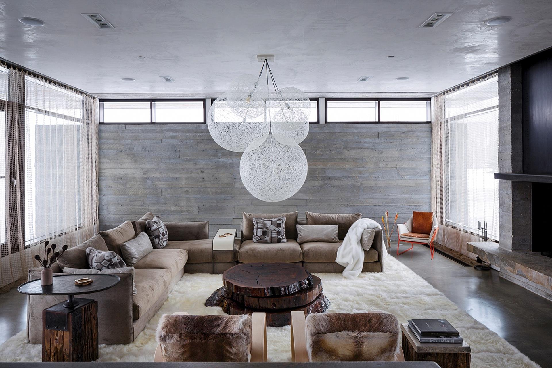 Na sala de estar, o sofá modular repousa sobre o amplo tapete de pele de ovelha e é combinado à mesa, composta por lâminas de uma tora de nogueira, e à luminária da Moooi (Imagem do NYT, usar apenas no respectivo material)