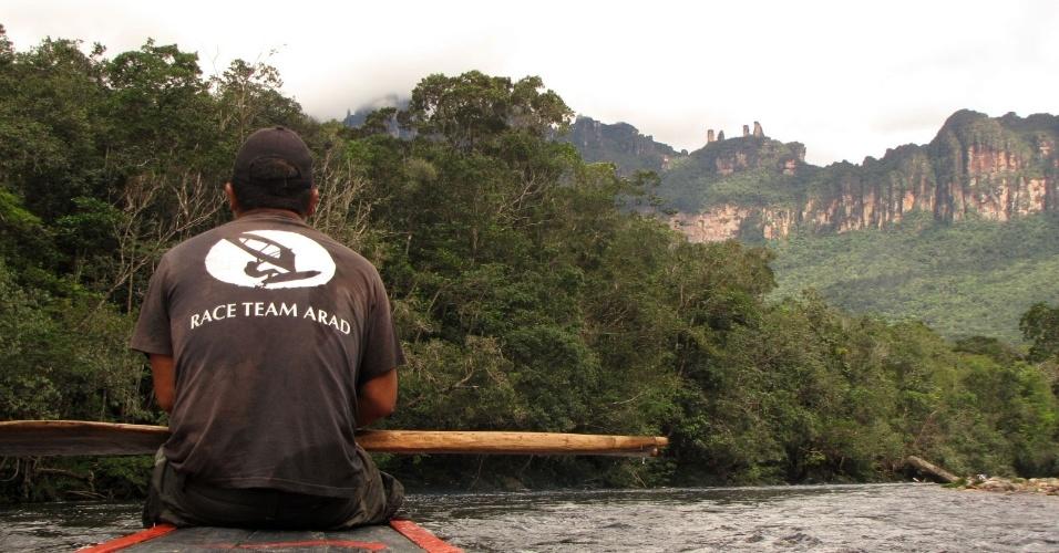 Barqueiro observa o rio e direciona seu companheiro durante a viagem