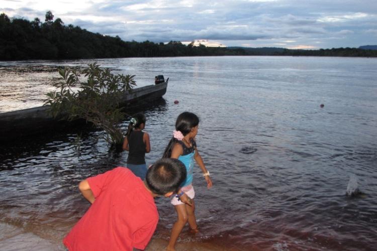 Entardecer na Lagoa Canaima. Crianças se divertem atirando pedrinha na água