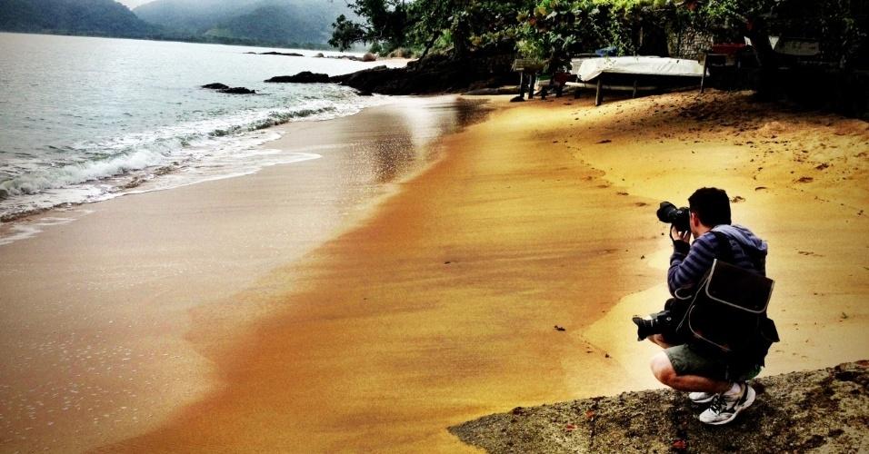 Viajante tira foto da praia da Vila Picinguaba, um vilarejo de pescadores com mais de 400 anos de história que, apesar de hoje pontuada por alguns empreedimentos hoteleiros luxuosos, ainda preserva um clima de lugar pacato