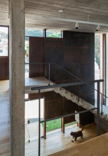 Na face interna da fachada frontal da Casa Pepiguari, em São Paulo, está uma escada de concreto moldada