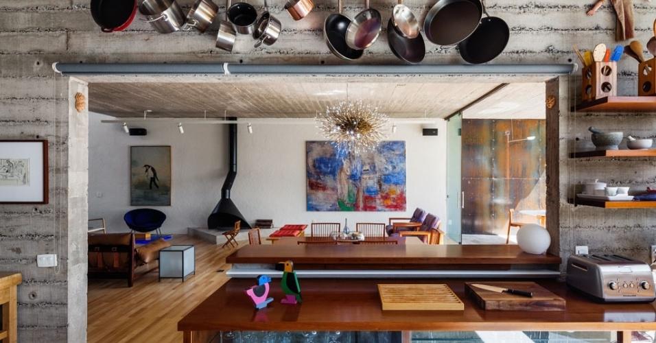 A cozinha integra-se à ampla sala de estar com jantar e lareira a partir de um rasgo na parede estrutural de concreto, que forma um passa-prato. A marcenaria da cozinha é estruturada por madeira ipê e vidro. Neste ambiente, uma das parede e a laje também mostram o concreto nu, sem lixamentos nem resinas. A Casa Pepiguari foi projetada por Marcelo Ferraz e fica em São Paulo