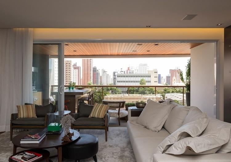A varanda do apartamento em Campinas (SP) é uma extensão da sala de estar e tem vista para o bairro do Cambuí. No estar, o sofá de cor clara e as poltronas cinzas são da Artzzi. A decoração do imóvel é um projeto da arquiteta Elaine Carvalho