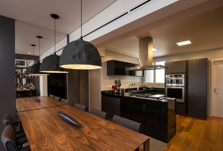 Integrada à cozinha, a sala de jantar tem mesa assinada pelo designer Jader Almeida. O móvel de geometria simples é combinado aos pendentes Rock, da italiana Foscarini em parceria com a Diesel. Por fim, o espelho na parede dá a sensação de amplitude ao ambiente. O projeto de interiores do apartamento em Campinas (SP) é uma criação da arquiteta Elaine Carvalho