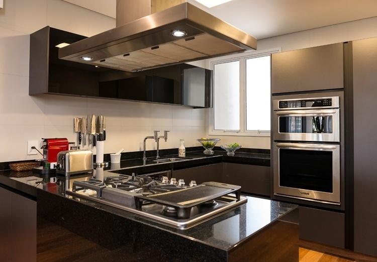 Na cozinha, a bancada com pia e cooktop é feita de granito preto e o painel (Kitchens) - revestido por laminado melamínico cinza chumbo - abriga os fornos embutidos. O projeto de interiores do apartamento em Campinas (SP) é assinado pela arquiteta Elaine Carvalho