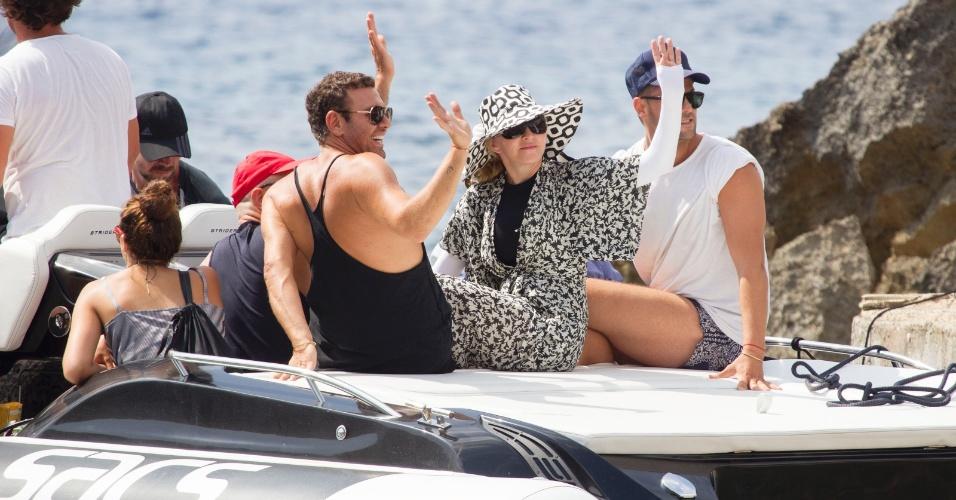 19.ago.2014 - Ao lado de amigos e com o corpo coberto, Madonna acena após entrar em barco em Ibiza, na Espanha