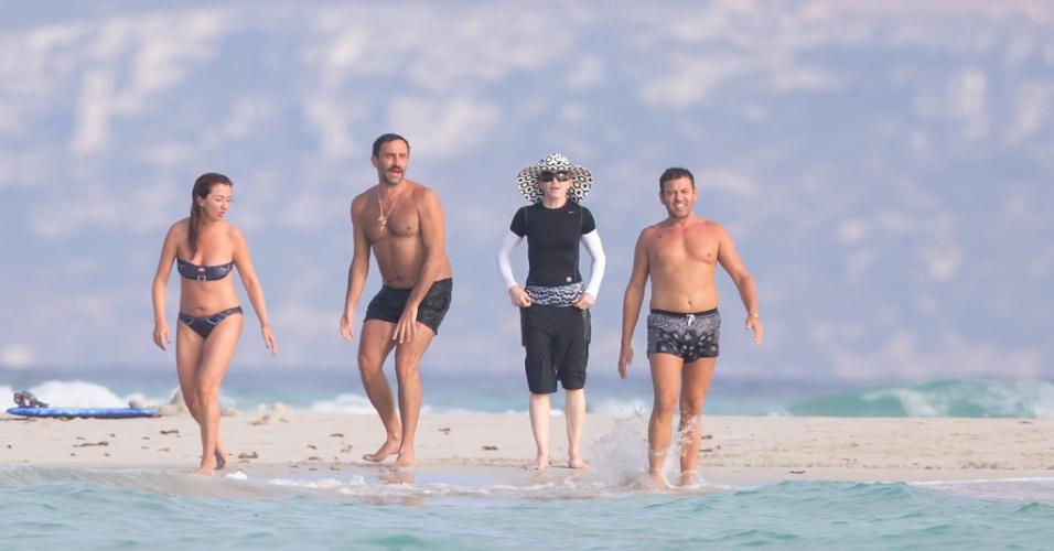 19.ago.2014 - Ao lado de amigos, Madonna caminha em praia de Ibiza, na Espanha, usando chapéu, bermuda e mangas compridas