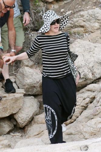 19.ago.2014 - Madonna caminha em praia de Ibiza, na Espanha, totalmente coberta, com calças, blusa de manga comprida e chapéu