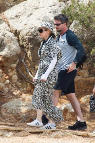 19.ago.2014 - Usando um roupão preto e branco e mangas compridas, Madonna anda coberta em praia de Ibiza, na Espanha