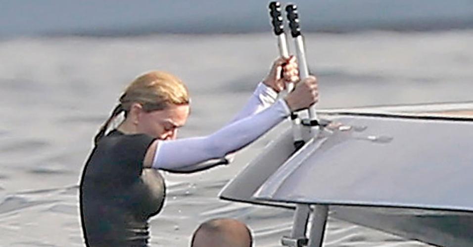 19.ago.2014 - Usando uma camiseta preta e mangas compridas brancas, Madonna sobe em iate após dar mergulho no mar de Ibiza, na Espanha