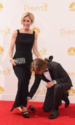 25.ago.2013 -  Felicity Huffman passou por situação embaraçosa ao cruzar o tapete vermelho do Emmy. Sua sandália abriu e ela precisou da ajuda do marido, o ator  William H. Macy