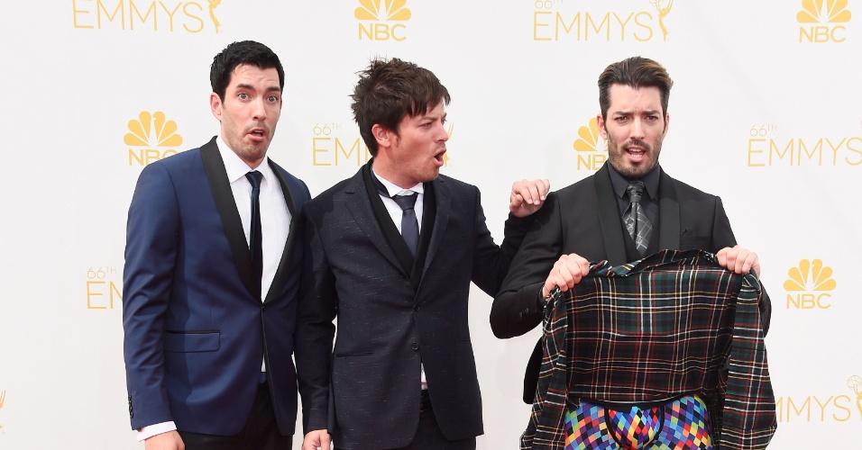 25.ago.2014 -  O comediante Jonathan Silver Scott levanta a saia no tapete vermelho da 66ª edição do Emmy Awards, em Los Angeles, para espanto dos irmãos Drew Scott e J.D. Scott