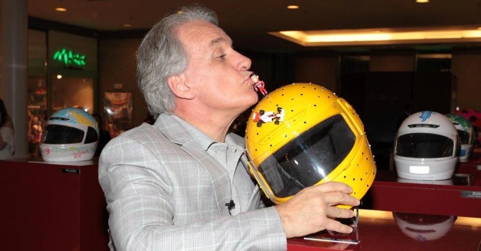 26.ago.2014 - Otávio Mesquita beija boneco de Ayrton Senna na abertura da exposição