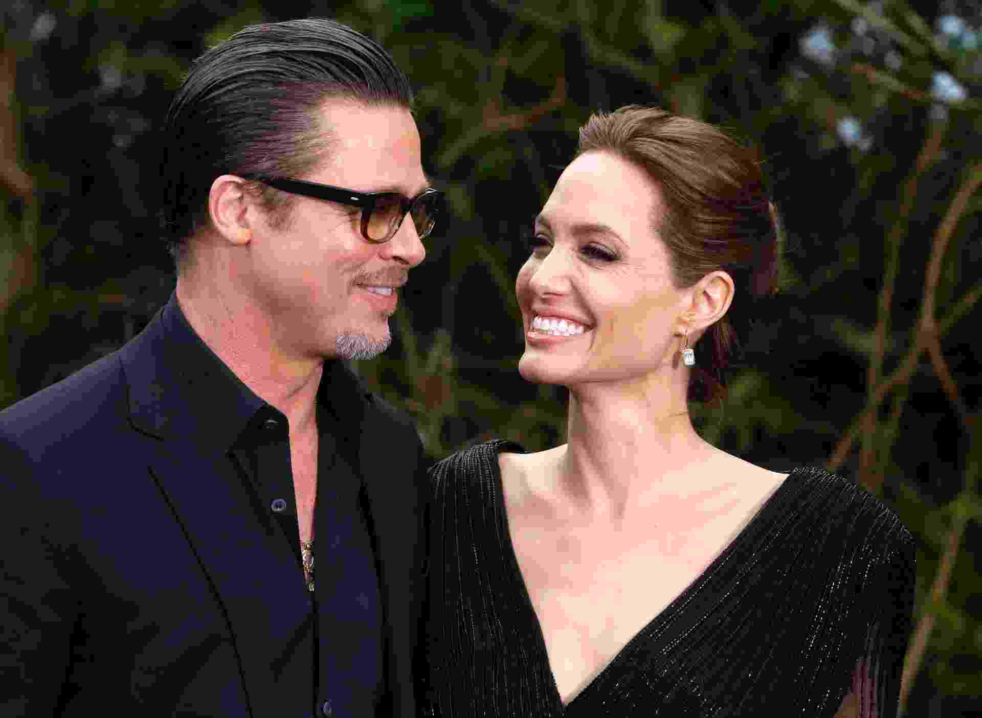"""8.mai.2014 - Brad Pitt e Angelina Jolie sorriem ao chegar para exibição dos figurinos de """"Malévola"""" no Palácio de Kensington, em Londres - Luke MacGregor/Reuters"""