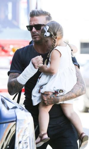 29.ago.2014 - Com a mão enfaixada, David Beckham chega no Aeroporto Internacional de Los Angeles com os filhos Romeo, Cruz e Harper no colo