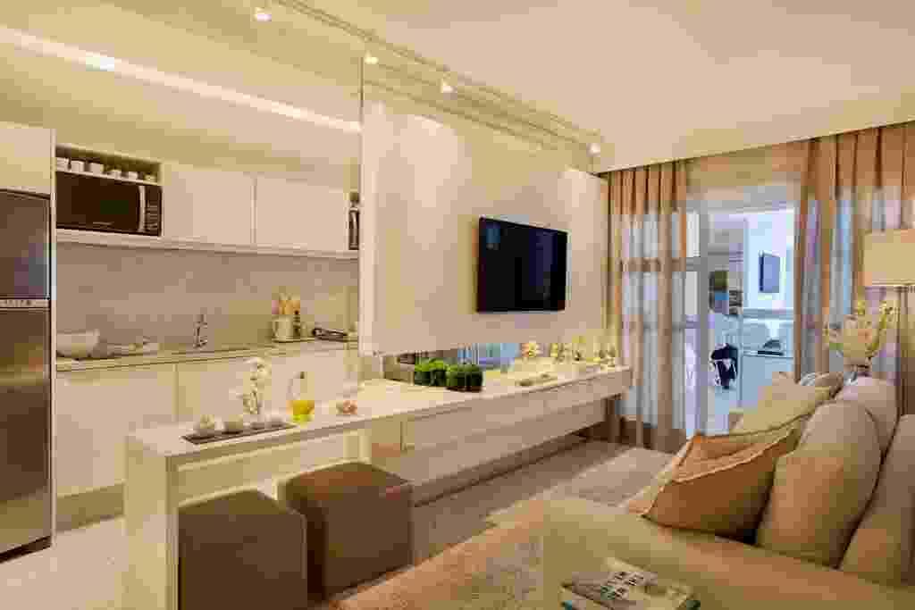 Na proposta da arquiteta Izabela Lessa, o living (17 m²) está integrado à cozinha. Aqui, o destaque fica por conta da parede espelhada que apoia o painel da TV. A marcenaria também faz a diferença: cria um aparador com gaveteiro e uma pequena bancada que abriga sob si os pufes, que podem ser usados em pequenas refeições ou em eventos sociais - MCA Estúdio/ Divulgação