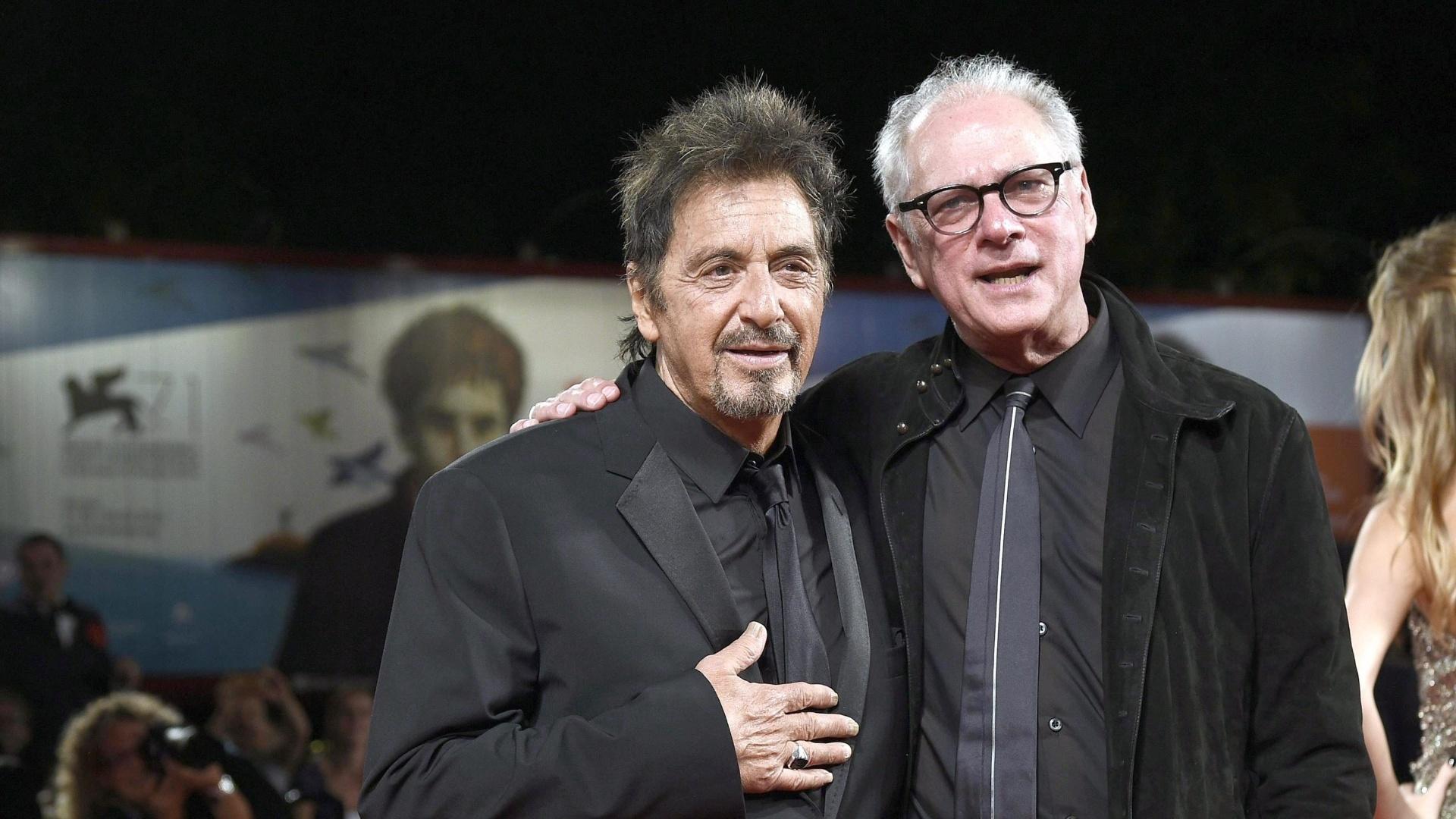 30.ago.2014 - Al Pacino abraça o diretor Barry Levinson ao chegar ao tapete vermelho do filme