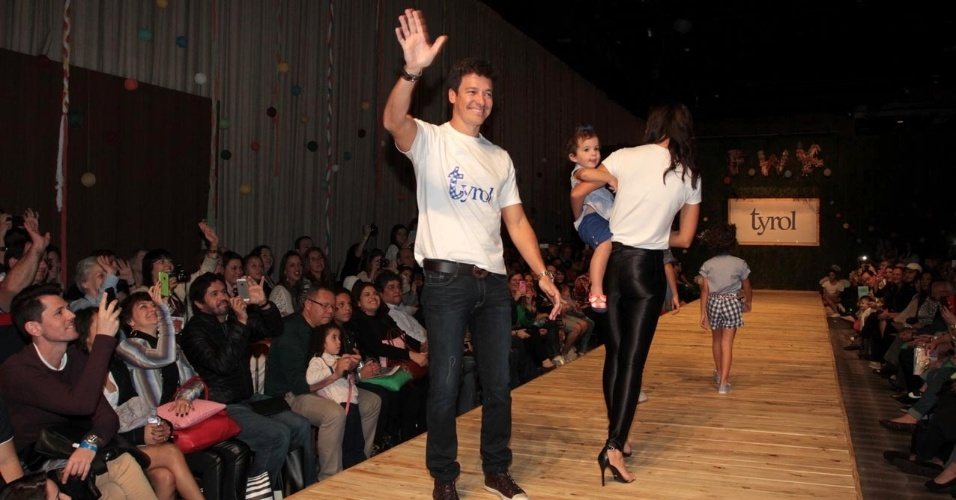 30.ago.2014 - Rodrigo Faro acena para o público do Fashion Weekend Kids ao desfilar com a mulher, Vera Viel, e as três filhas do casal