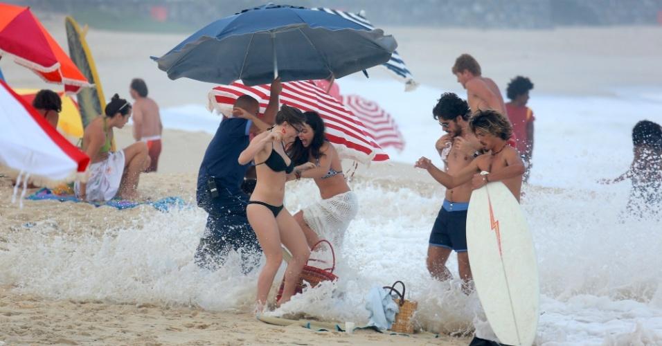 """4.set.2014 - Durante a gravação, os atores de """"Boogie Oogie"""" foram surpreendidos por uma onda, que avançou sobre seus pertences que estavam na areia, além de quase derrubar o guarda sol. Apesar do imprevisto, eles caíram na gargalhada"""