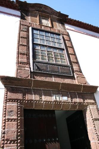 Fachada da Casa Riquel, erguida no século 18; o destaque de sua porta principal construída de pedra vermelha que inclui o brasão da família que dá nome ao local