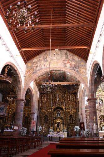 Interior de igreja em Tenerife onde predomina o estilo barroco, com teto de madeira e colunas de pedra vulcânica local