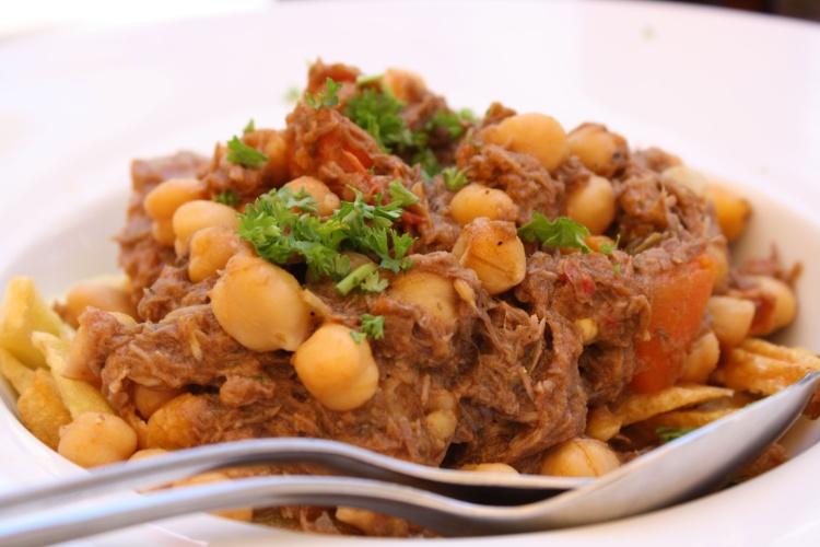 """""""Ropa vieja"""": carne bovina cozida e desfiada, servida com grão-de-bico e batatas fritas"""