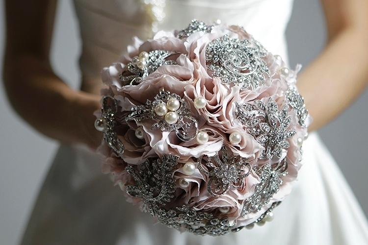 Buquê com flores de tecido e broches prateados e pérolas, da Bouquet Boutique, R$ 900