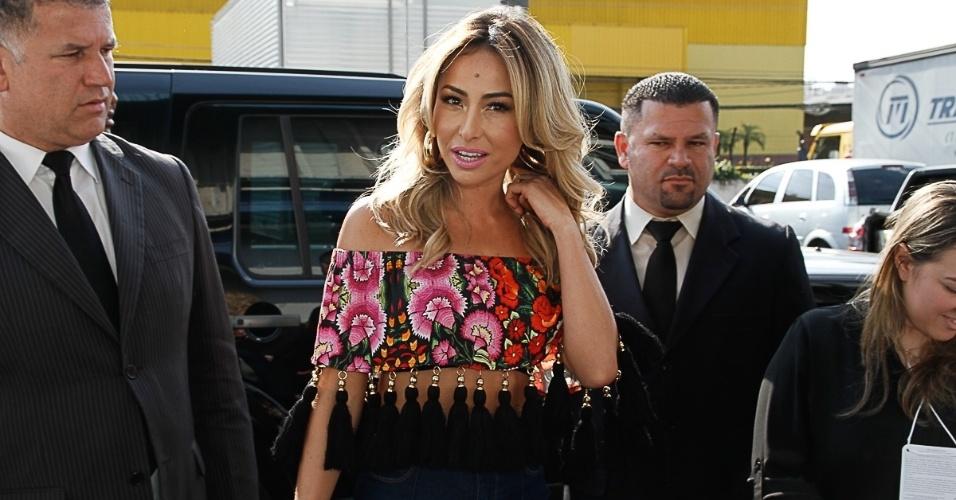 7.set.2014 - Com uma blusa tomara que caia toda estampado e com uns penduricalhos pretos, Sabrina Sato chama atenção em uma feira internacional de beleza, que acontece em São Paulo