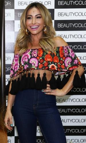 7.set.2014 - Com uma blusa tomara que caia todo estampado e com uns penduricalhos pretos, Sabrina Sato chama atenção em uma feira internacional de beleza
