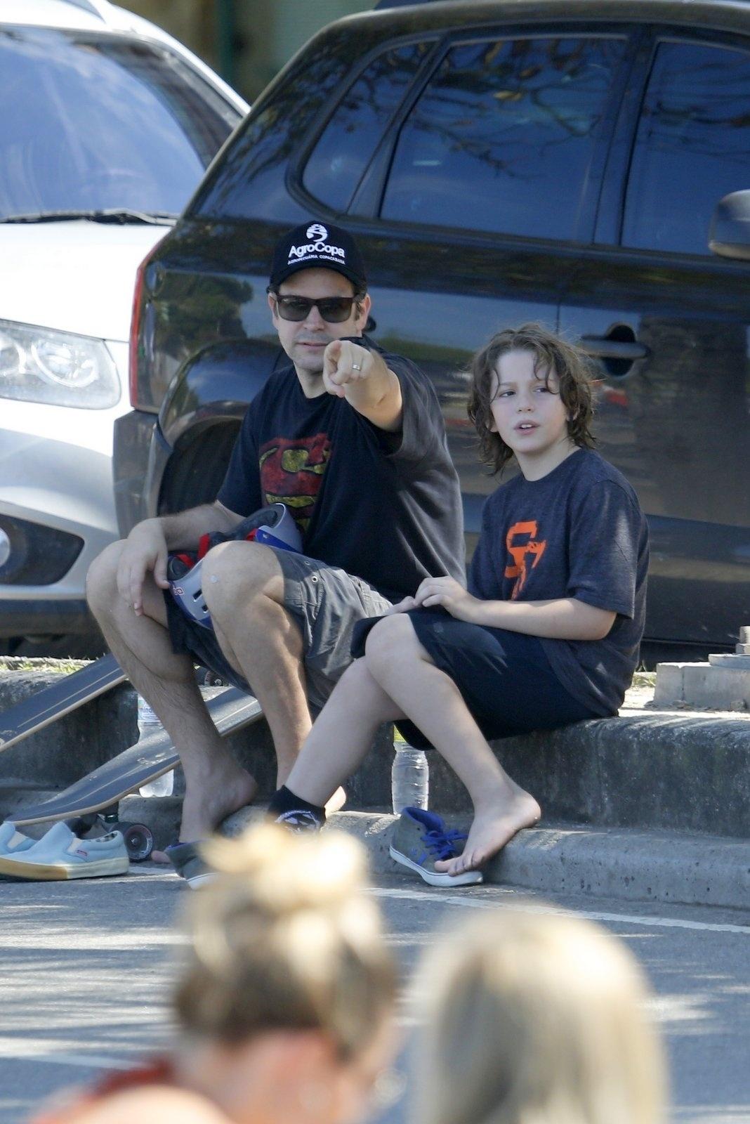 Murilo Benício anda de skate com o filho Pietro na orla do Leblon