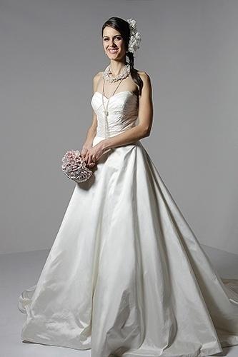 Noiva romântica: com muitas pérolas e flores, é possível transformar o vestido básico em um look romântico. Como o acessório de cabeça é feito com flores naturais preservadas, o buquê de broches ajuda a equilibrar o visual delicado