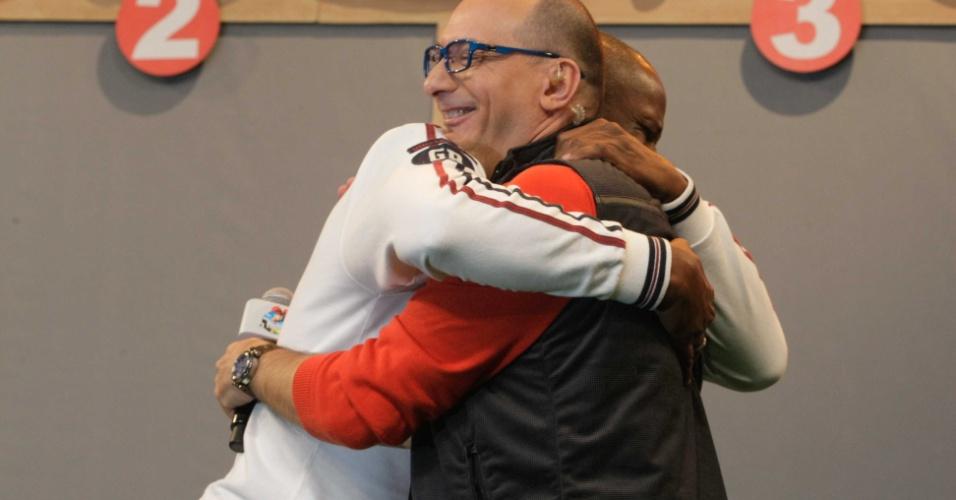10.set.2014 - Britto Jr dá abraço em Robson Caetano durante coletiva de imprensa da sétima edição de