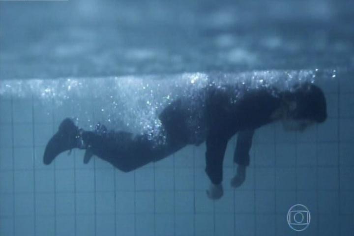 11.set.2014 - No momento em que Duda e Ângela conversam sobre a morte de Bruno, o flashback mostra as duas pegando o corpo do rapaz de dentro do freezer e jogando na piscina