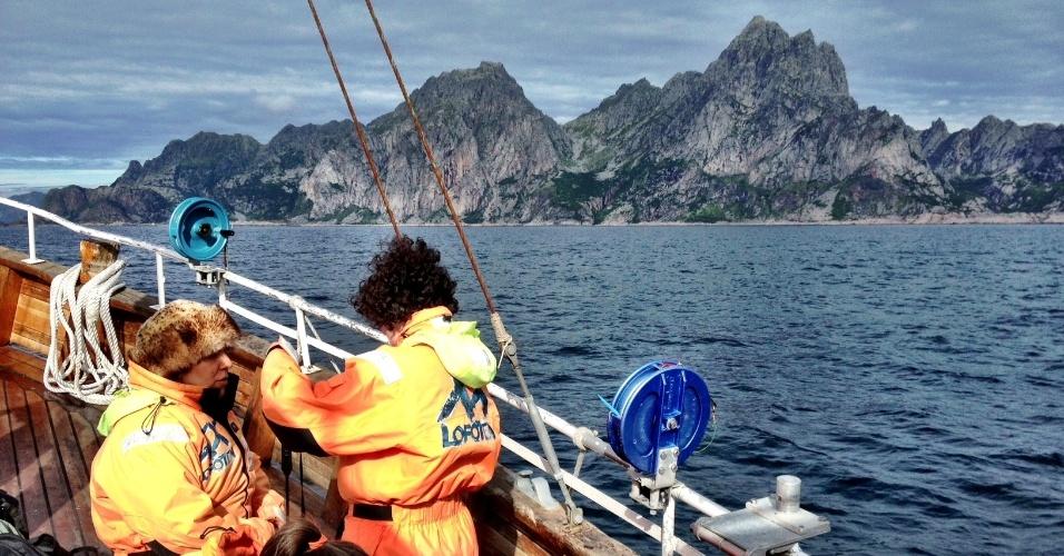Viajantes observam as montanhas das ilhas Lofoten durante passeio de barco entre Svolvær e Henningsvær