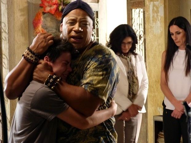 Xana (Ailton Graça) e Luciano (Yago Machado) choram na hora da despedida do garoto que é levado para um orfanato