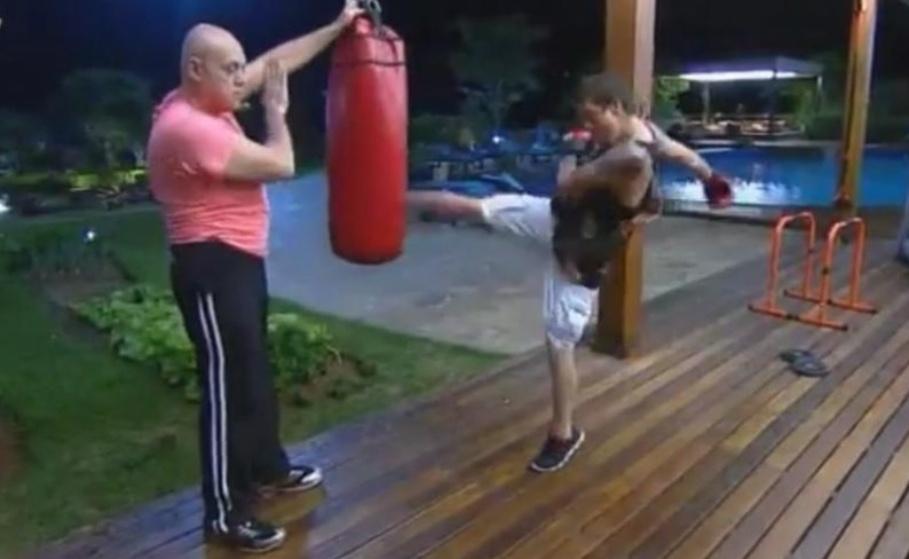 16.ago.2014 - DH chuta saco de pancadas e recebe ajuda de Oscar Maroni para malhar em
