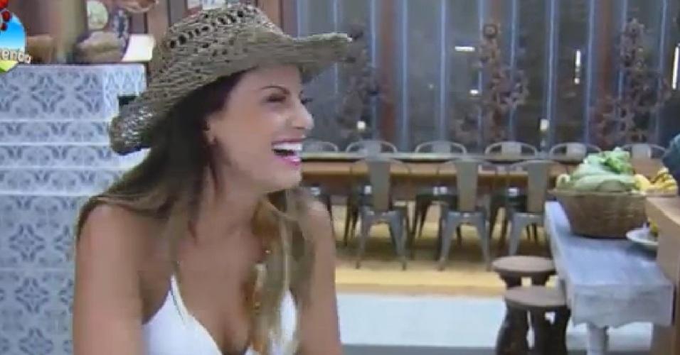 16.set.2014 - Babi Rossi conversa enquanto limpa a pia