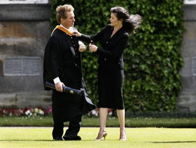 21.jun.2006 - Catherine Zeta-Jones arruma a roupa de Michael Douglas, que se prepara para ser fotografado para receber seu prêmio honorário na Universidade de St Andrews na Escócia