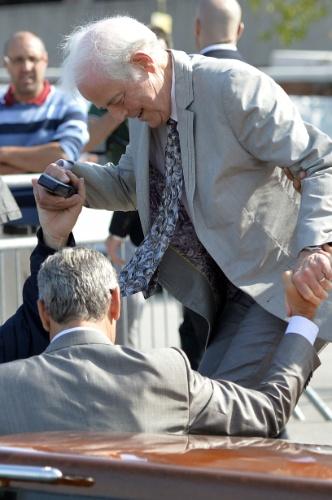 26.set.2014 - George Clooney ajuda seu pai, Nick Clooney, a descer de um táxi-barco ao chegar em Veneza, na Itália, onde o ator se casa neste sábado com Amal Alamuddin
