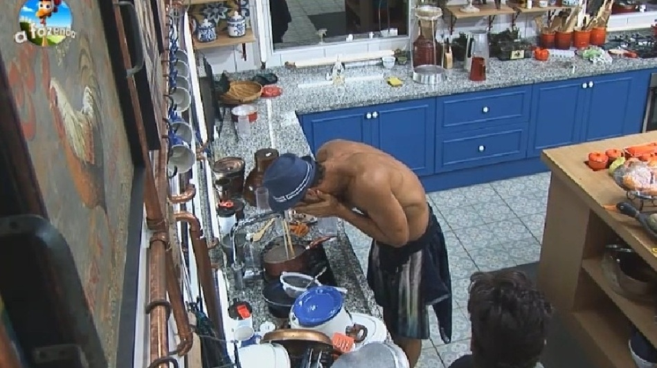 """26.set.2014 - Diego Cristo lava o rosto na pia da cozinha enquanto conversa com Léo Rodriguez na cozinha de """"A Fazenda 7"""", na madrugada deste sábado"""