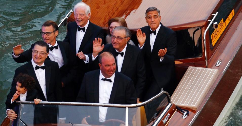 O ator George Clooney bate palmas junto com convidados em um táxi aquático de Veneza, a caminho de um jantar de gala que antecede o seu casamento com a advogada Amal Alamuddin.