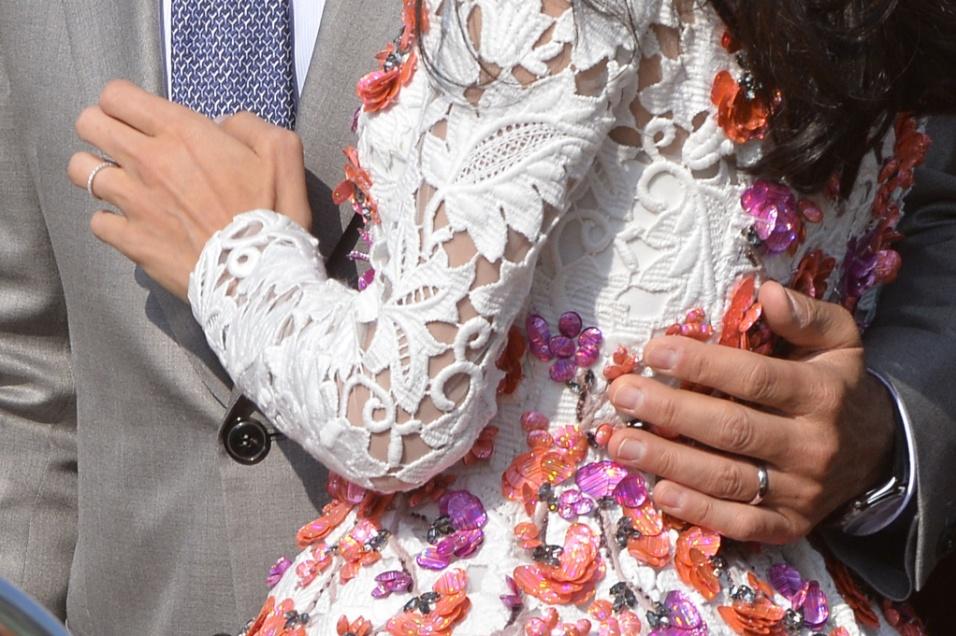 28.set.2014 - Foto mostra o detalhe das alianças nas mãos de George Clooney e de sua mulher, Amal Alamuddin, enquanto navegam, em um táxi aquático, no Grande Canal de Veneza, após deixarem o hotel Aman, onde a cerimônia foi realizada no sábado.