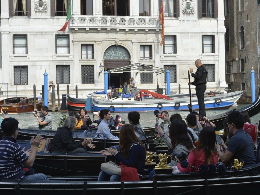 28.set.2014 - Turistas passeiam em gôndolas no Grande Canal de Veneza e tiram fotos do hotel Aman, onde o ator George Clooney e a advogada britânica Amal Alamuddin celebraram seu casamento neste sábado.
