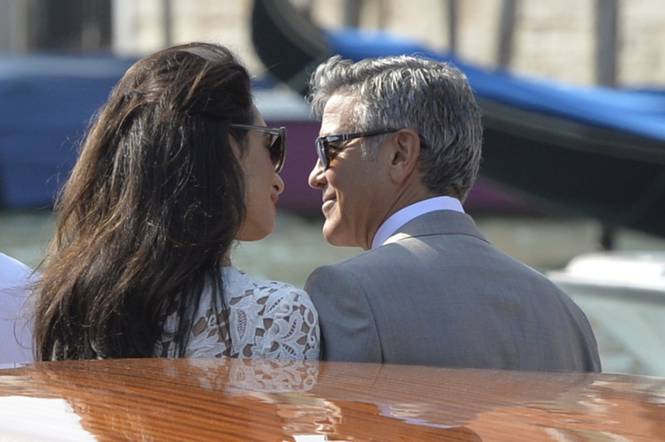 28.set.204 - O ator George Clooney e sua mulher, a advogada Amal Alamuddin, trocam olhares em um táxi aquático, no Grande Canal de Veneza, neste domingo.