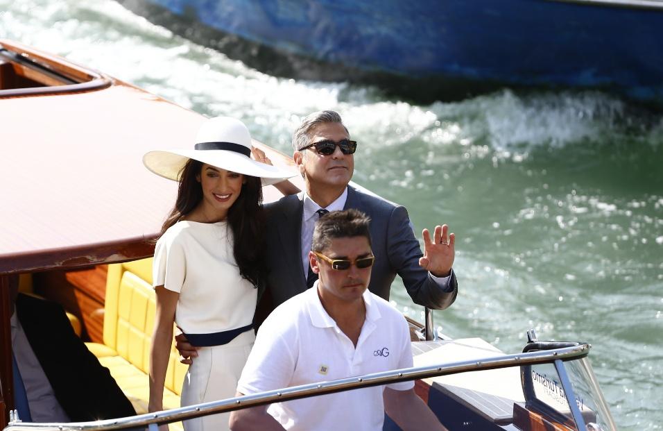 29.set.2014 - Ao lado da mulher Amal Alamuddin, George Clooney acena para fãs e fotógrafos após se casar em cerimônia civil na prefeitura de Veneza