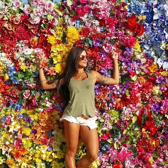 29.set.2014- Aline Riscado curte férias Miami. Ex-bailarina do Faustão não resistiu a um painel de flores perto da praia