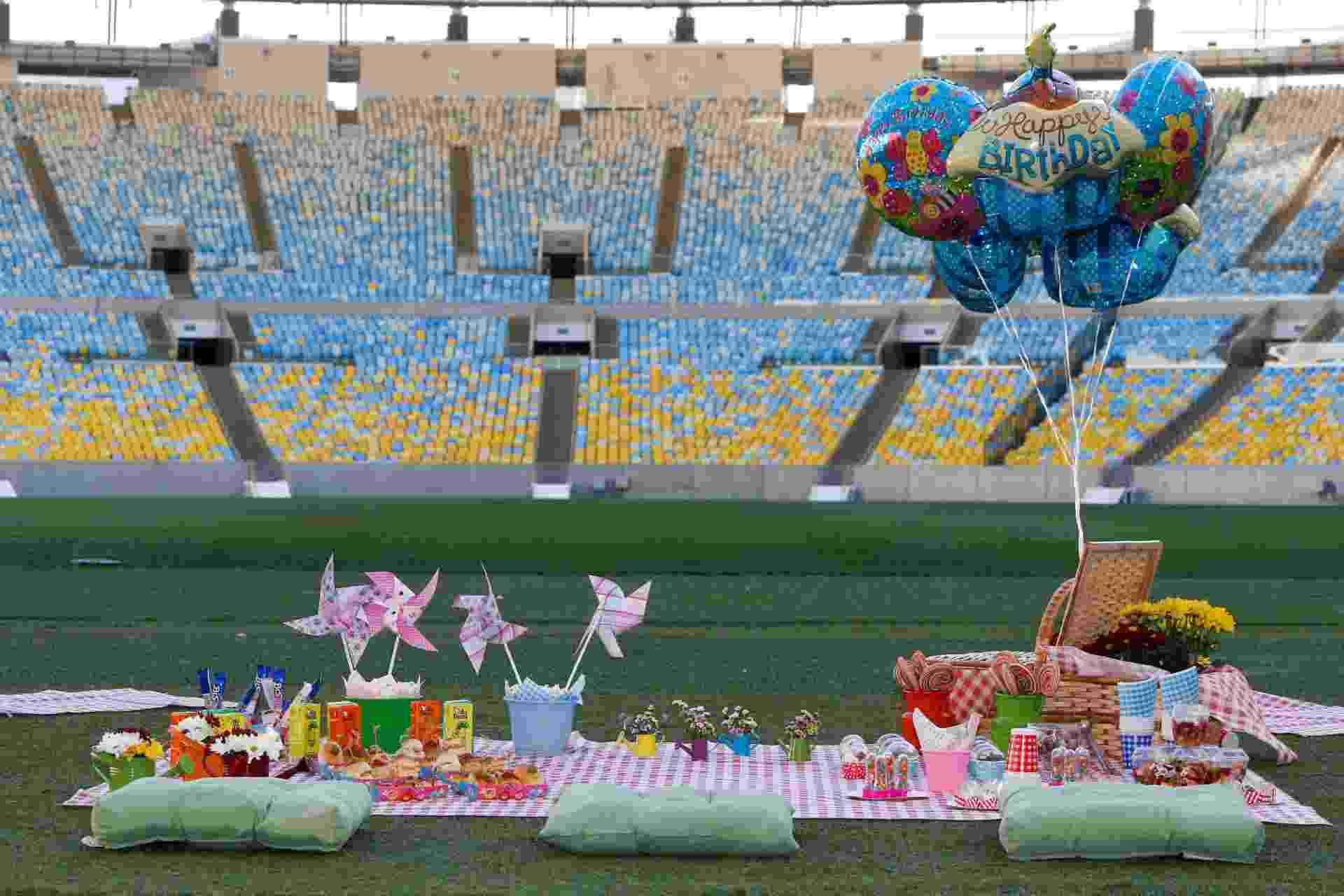 """Um dos principais estádios do Brasil, o Maracanã, no Rio de Janeiro, tornou-se opção para a comemoração de aniversários com o """"Piquenique Show de Bola"""". Sobre a grama sintética dos setores Norte e Sul do estádio, são colocadas toalhas xadrezes e almofadas, de acordo com o número de convidados do evento, que pode receber de 20 a 50 pessoas - Staff Images"""