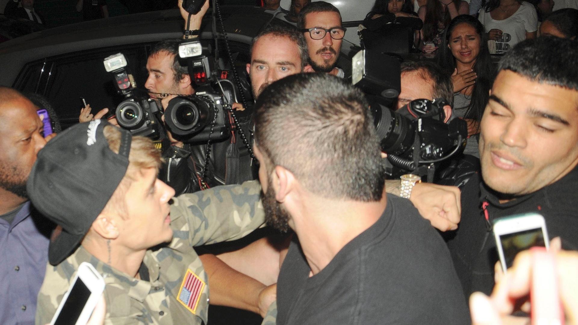 30.set.2014 - Justin Bieber dá soco em paparazzo ao tentar entrar no hotel em que está hospedado em Paris